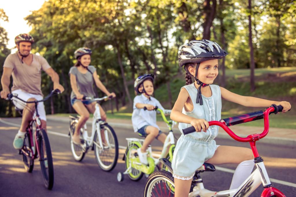 Rodzina jedzie na wygodnych rowerach, dziewczynka i chłopiec jadą na rowerach dziecięcych